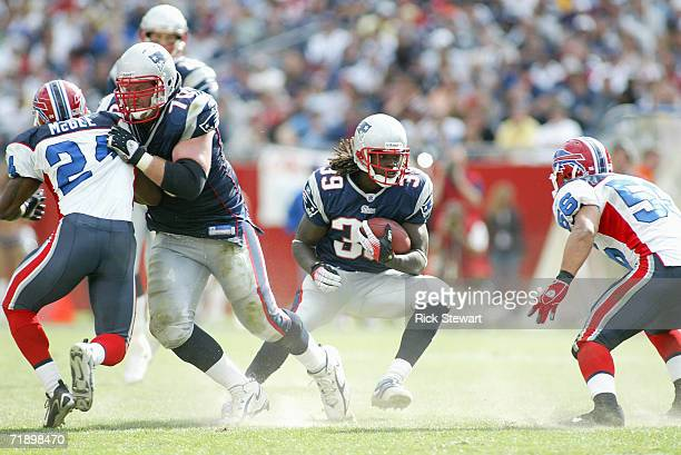 Laurence Maroney of the New England Patriots runs the ball for yardage as teammate Logan Mankins blocks Terrence McGee of the Buffalo Bills on...