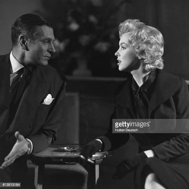 Laurence Olivier introduces Marilyn Monroe to a press conference at the Savoy Hotel in London as the costar to his film The Sleeping Prince which was...
