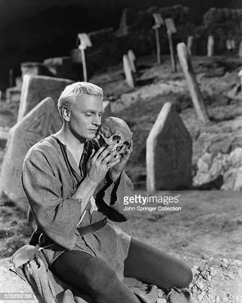 Laurence Olivier is holding a skull in a cemetery in a scene from the movie Hamlet