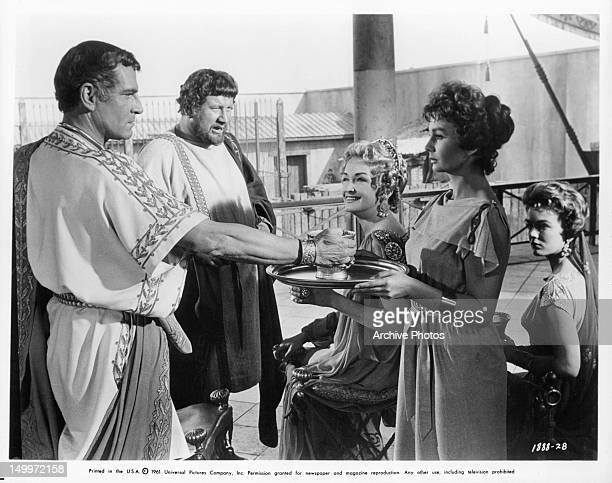 Laurence Olivier is served wine by Jean Simmons as Peter Ustinov Nina Foch and Joanna Barnes watch in a scene from the film 'Spartacus' 1960