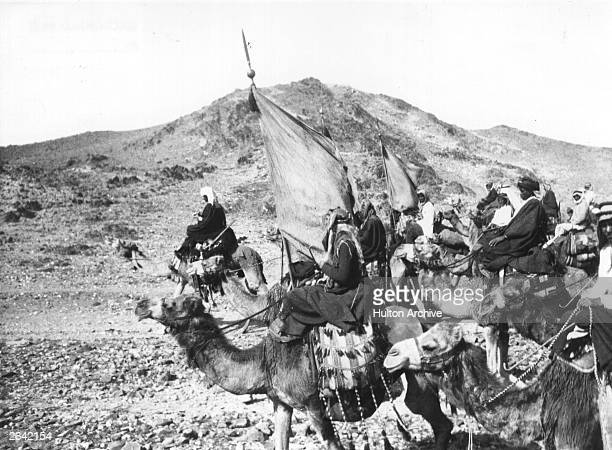 TE Laurence's Arab guerrillas riding on camels in the desert