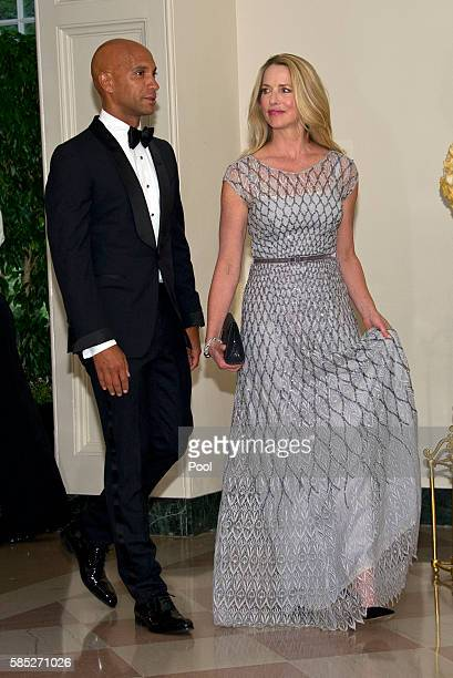 Laurene Powell Jobs Founder Emerson Collective and former Washington DC Mayor Adrian Fenty arrive at the White House August 2 2016 in Washington DC...