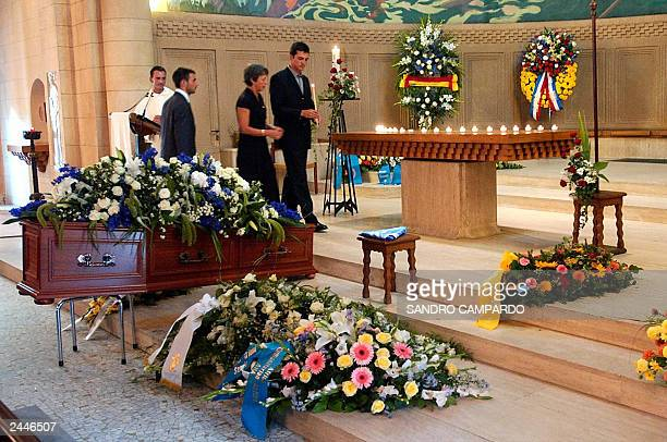 Laurent and Adrian de Mello , sons of Sergio Vieira de Mello, and his wife Annie light a candel near the coffin containing the body of Brazilian...