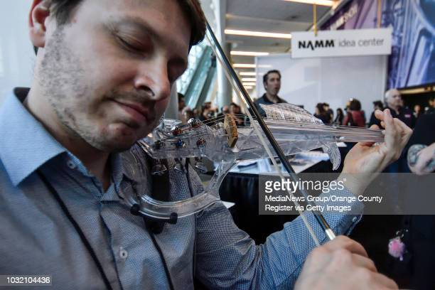 Laurent Bernadac of 3dvarius shows off their fivestring acrylic electric violin during a media preview at NAMM in Anaheim California on Wednesday...
