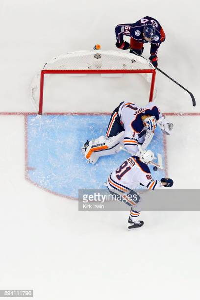 Laurent Brossoit of the Edmonton Oilers covers up a loose puck as Yohann Auvitu of the Edmonton Oilers defends the crease during the game against the...