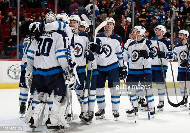 Laurent Brossoit of the Winnipeg Jets is congratulated by teammates after their win in their NHL game against the Vancouver Canucks at Rogers Arena...