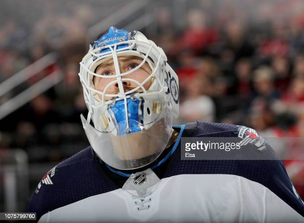 Laurent Brossoit of the Winnipeg Jets looks up during a stop in play in the overtime period against the New Jersey Devils at Prudential Center on...