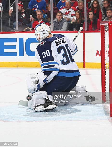 Laurent Brossoit of the Winnipeg Jets makes a pad save against the New Jerset Devils during the game at Prudential Center on December 1 2018 in...