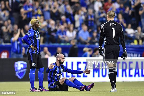 Laurent Ciman of the Montreal Impact reacts as he sits on the pitch while teammates Ambroise Oyongo and Evan Bush walk towards him during leg one of...
