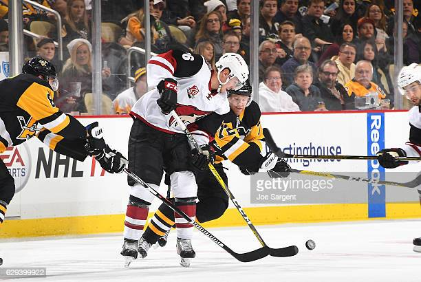 Laurent Dauphin of the Arizona Coyotes handle the puck against Patric Hornqvist of the Pittsburgh Penguins at PPG Paints Arena on December 12 2016 in...