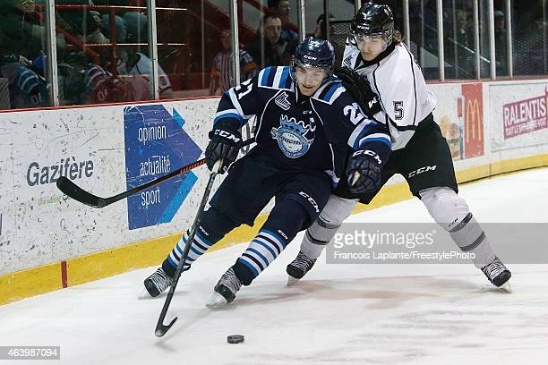 Laurent Dauphin of the Chicoutimi Sagueneens controls the puck as Elie Berube of the Gatineau Olympiques defends on February 20, 2015 at Robert...