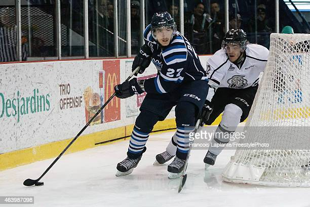 Laurent Dauphin of the Chicoutimi Sagueneens controls the puck against Mickael Beauregard of the Gatineau Olympiques on February 20, 2015 at Robert...