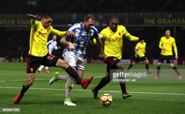 Laurent Depoitre of Huddersfield Town is challenged by Jose Holebas of Watford and Christian Kabasele of Watford during the Premier League match...