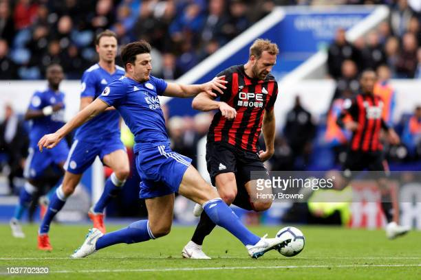 Laurent Depoitre of Huddersfield Town is tackled by Harry Maguire of Leicester City during the Premier League match between Leicester City and...