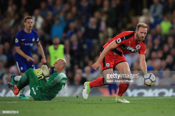 Laurent Depoitre of Huddersfield Town scores the opening goal after colliding with Chelsea goalkeeper Willy Caballero during the Premier League match...
