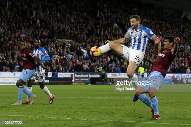 Laurent Depoitre of Huddersfield Town stretches for the ball under pressure from Fabian Balbuena of West Ham United during the Premier League match...