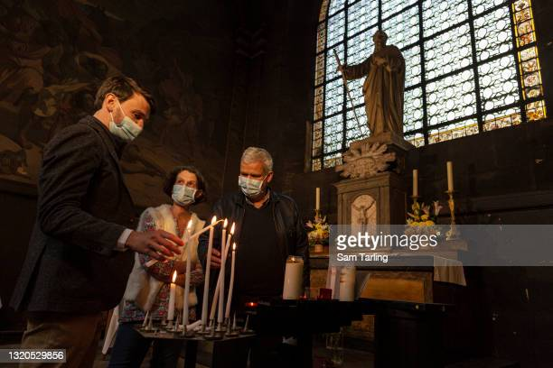 Laurent Frémont, an activist calling for a legal right for people to visit hospital patients, lights a candle at a service in memory of those who...