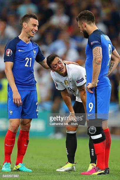Laurent Koscielny and Olivier Giroud of France console Mesut Ozil of Germany at the end of the UEFA Euro 2016 Semi Final match between Germany and...