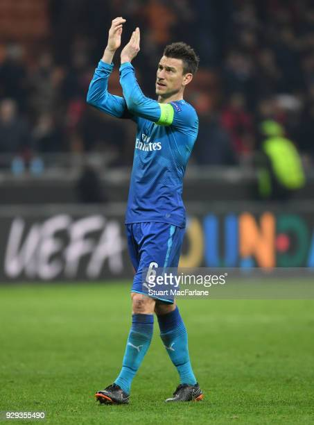 Laurent Koscielny applauds the Arsenal fans after the UEFA Europa League Round of 16 match between AC Milan and Arsenal at the San Siro on March 8...