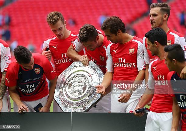 Laurent Koscielny Calum Chambers Olivier Giroud Mathieu Flamini Aaron Ramsey Mikel Arteta and Alexis Sanchez of Arsenal look at the trophy after...
