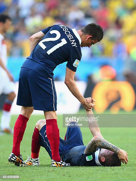 Laurent Koscielny consoles Mathieu Debuchy of France after being defeated by Germany 10 during the 2014 FIFA World Cup Brazil Quarter Final match...