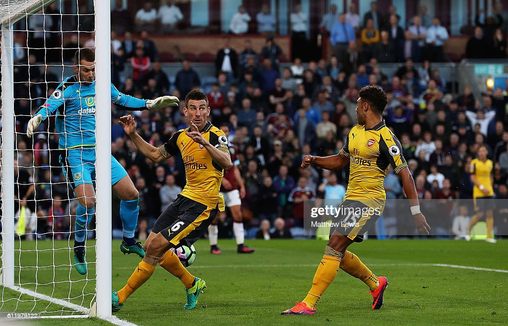 Laurent Koscielny defelcts (R) Alex Oxlade-Chambelrain's shot to score the Arsenal goal during the Premier League match between Burnley and Arsenal at Turf Moor on October 2, 2016 in Burnley, England.