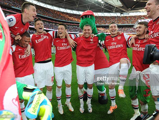 Laurent Koscielny Kieran Gibbs Olivier Giroud Mesut Ozil Lukas Podolski Thomas Vermaelem Aaron Ramsey and Per Mertesacker celebrate after the FA Cup...