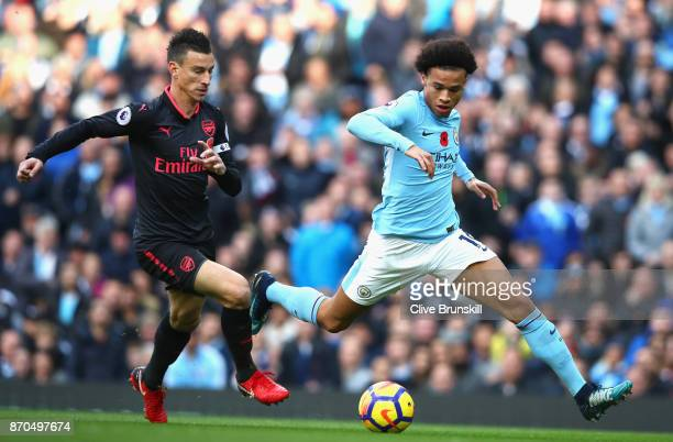 Laurent Koscielny of Arsenal and Leroy Sane of Manchester City battle for possession during the Premier League match between Manchester City and...