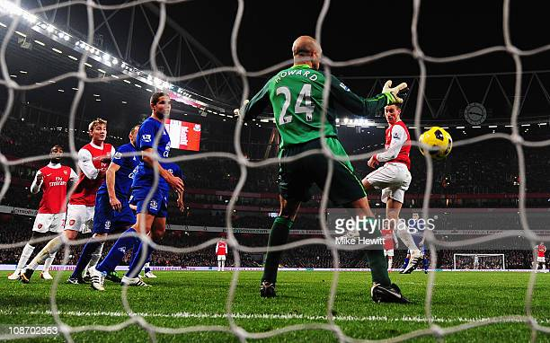 Laurent Koscielny of Arsenal beats Tim Howard of Everton to score their second goal during the Barclays Premier League match between Arsenal and...