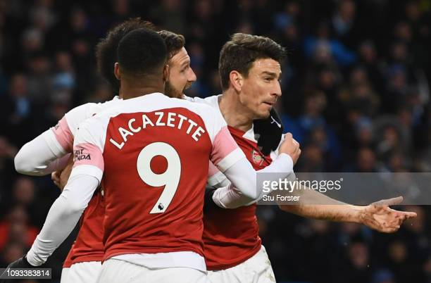 Laurent Koscielny of Arsenal celebrates after scoring his team's first goal with team mates during the Premier League match between Manchester City...