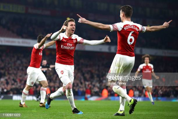 Laurent Koscielny of Arsenal celebrates with teammate Nacho Monreal after scoring his team's third goal during the Premier League match between...