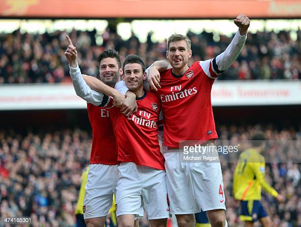 Laurent Koscielny of Arsenal celebrates with teammates Olivier Giroud of Arsenal and Per Mertesacker of Arsenal after scoring their third goal during...