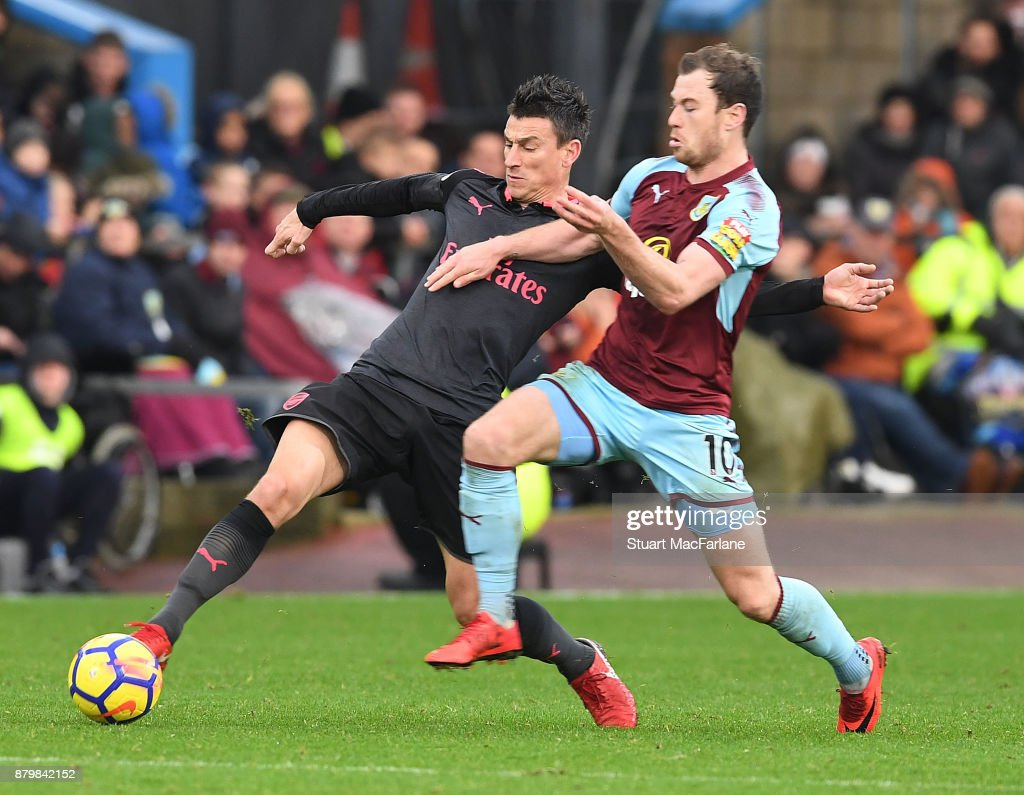 Laurent Koscielny of Arsenal challenged by Ashley Barnes of Burnley during the Premier League match between Burnley and Arsenal at Turf Moor on November 26, 2017 in Burnley, England.