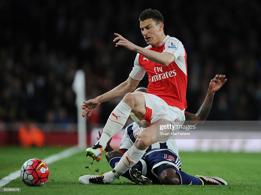 Laurent Koscielny of Arsenal challenged by Saido Berahino of WBA during the Barclays Premier League match between Arsenal and West Bromwich Albion at Emirates Stadium on April 21, 2016 in London, England.