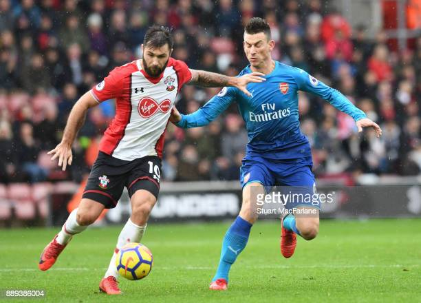 Laurent Koscielny of Arsenal challenges Charlie Austin of Southampton during the Premier League mat ch between Southampton and Arsenal at St Mary's...