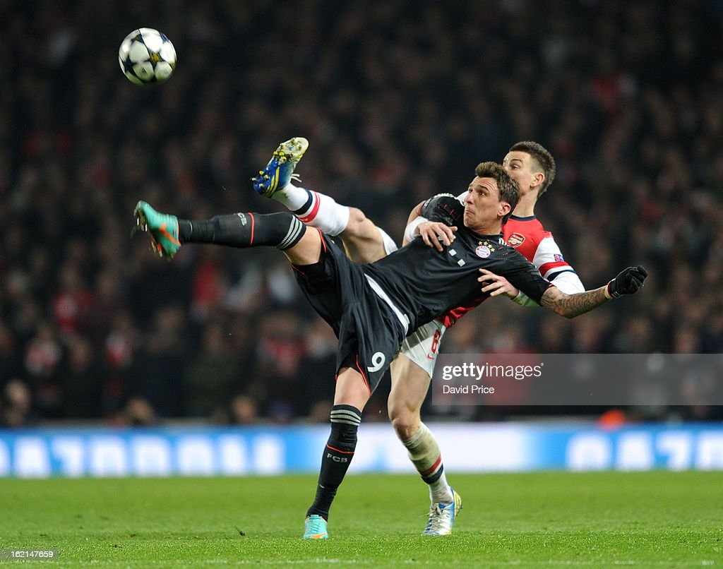 Laurent Koscielny of Arsenal challenges Mario Mandzukic of Bayern during the UEFA Champions League Round of 16 first leg match between Arsenal FC and Bayern Muenchen at Emirates Stadium on February 19, 2013 in London, England.