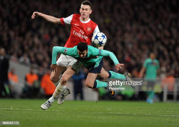 Laurent Koscielny of Arsenal clashes with Pedro Rodriguez of Barcelona during the UEFA Champions League round of 16 first leg match between Arsenal...