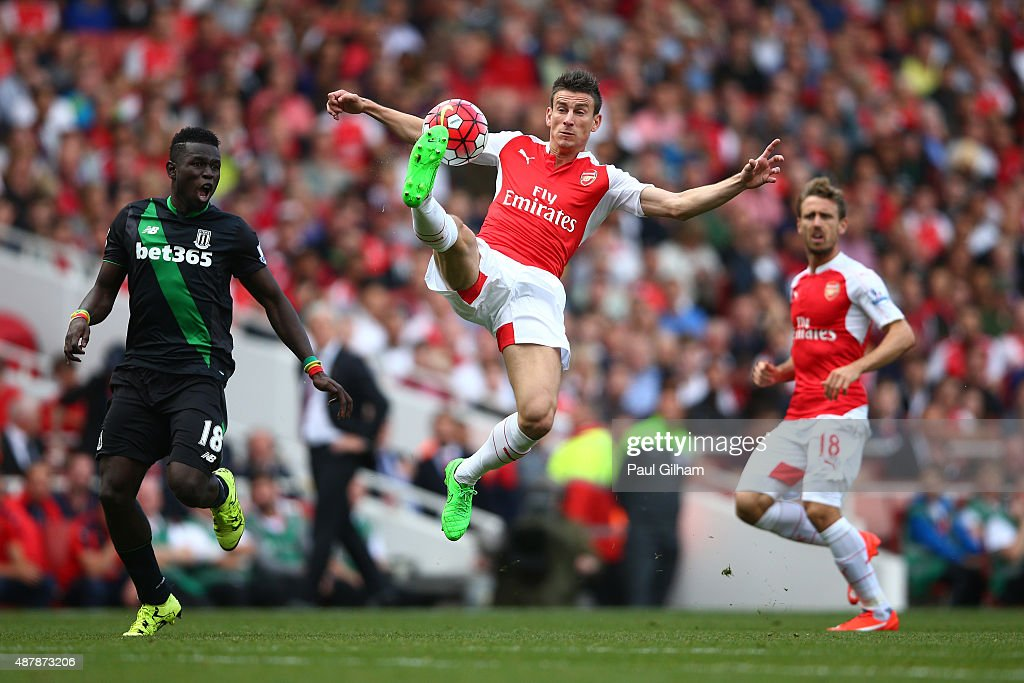 Laurent Koscielny of Arsenal controls the ball with Mame Biram Diouf of Stoke City during the Barclays Premier League match between Arsenal and Stoke City at the Emirates Stadium on September 12, 2015 in London, United Kingdom.