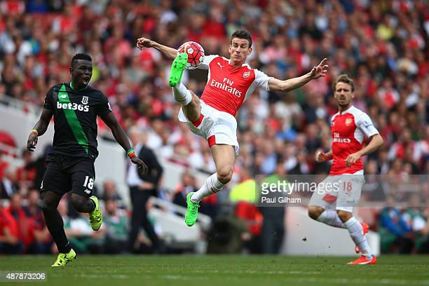 Laurent Koscielny of Arsenal controls the ball with Mame Biram Diouf of Stoke City during the Barclays Premier League match between Arsenal and Stoke...