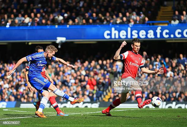 Laurent Koscielny of Arsenal fails to stop Andre Schurrle of Chelsea scores their second goal during the Barclays Premier League match between...