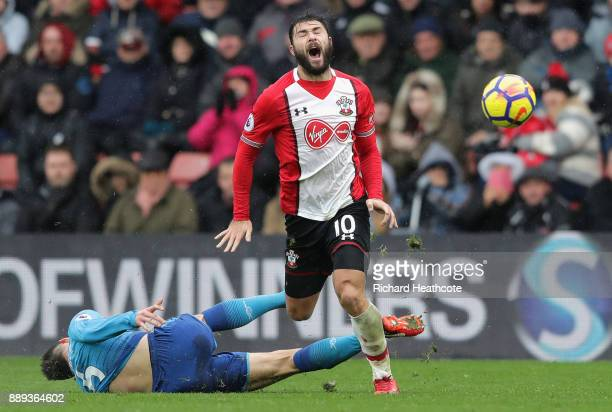 Laurent Koscielny of Arsenal goes down after clashing with Charlie Austin of Southampton during the Premier League match between Southampton and...
