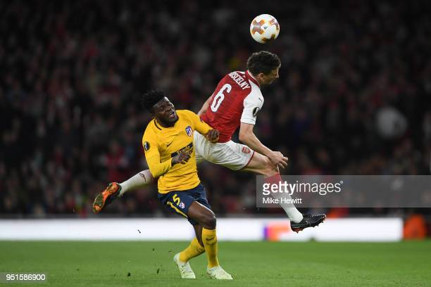 Laurent Koscielny of Arsenal is challenged by Thomas Partey of AtlŽtico Madrid during the UEFA Europa League Semi Final leg one match between Arsenal...