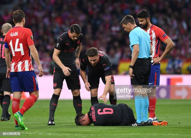 Laurent Koscielny of Arsenal is checked on by his team mates as he lies on the pitch injured during the UEFA Europa League Semi Final second leg...