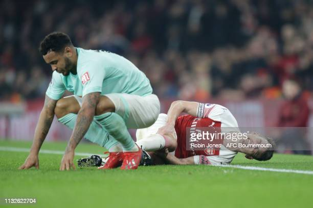 Laurent Koscielny of Arsenal is injured after he slides in to stop Joshua King of Bournemouth during the Premier League match between Arsenal FC and...