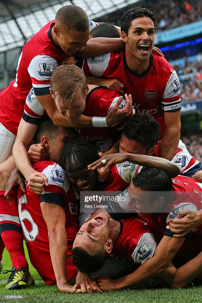 Laurent Koscielny of Arsenal is mobbed by his team mates after scoring their first goal during the Barclays Premier League match between Manchester City and Arsenal at Etihad Stadium on September 23, 2012 in Manchester, England.