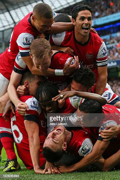 Laurent Koscielny of Arsenal is mobbed by his team mates after scoring their first goal during the Barclays Premier League match between Manchester...