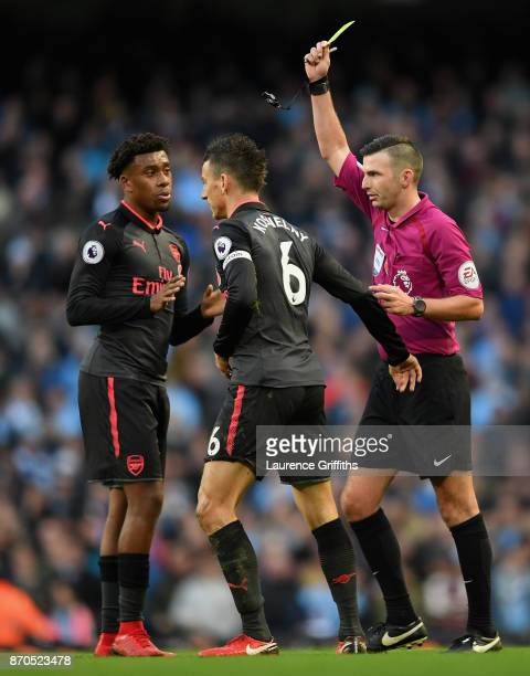 Laurent Koscielny of Arsenal is shown a yellow card by referee by referee Michael Oliver during the Premier League match between Manchester City and...