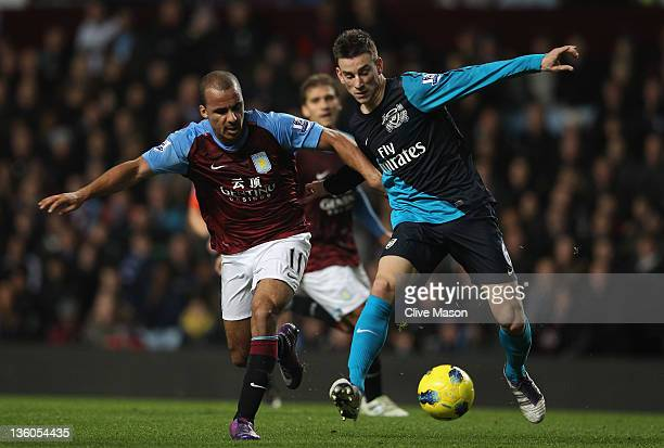 Laurent Koscielny of Arsenal is tackled by Gabby Agbonlahor of Aston Villa during the Barclays Premier League match between Aston Villa and Arsenal...