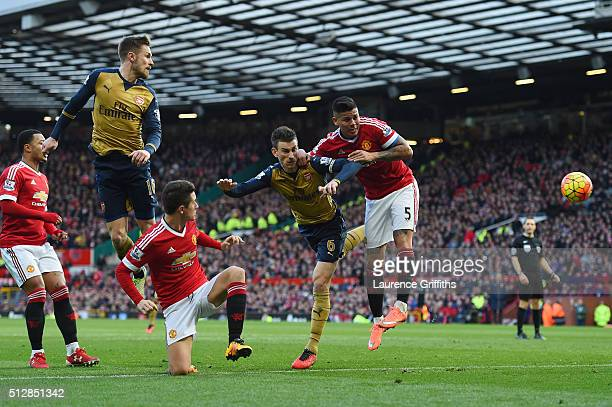 Laurent Koscielny of Arsenal jumps for a header with Marcos Rojo of Manchester United during the Barclays Premier League match between Manchester...