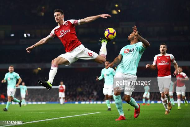 Laurent Koscielny of Arsenal jumps for the ball under pressure from Joshua King of AFC Bournemouth during the Premier League match between Arsenal FC...